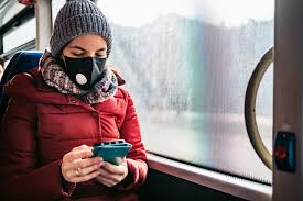 woman on train in mask with phone